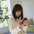 スマートフォンでデータ通信する女性
