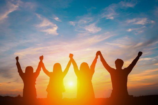 手をつないで手を上げる人々